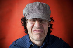 Man with a grimace of displeasure. On red background Royalty Free Stock Photography