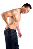 Man grimaces as he suffers from back pain. Man grimaces as he suffers from pain on lower back Royalty Free Stock Images