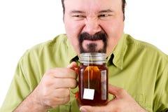 Man grimacing as he smells tea in a cup Stock Photos