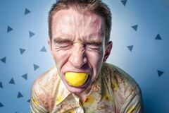 Man grimacing eating lemon Stock Photos