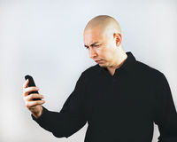 Man Grimacing at Smartphone Stock Photos