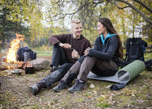 Man Grinding Coffee While Looking At Woman During Camping Stock Image