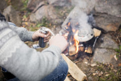Man Grinding Coffee Near Bonfire At Campsite. High angle midsection of man grinding coffee near bonfire at campsite Stock Image