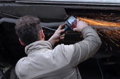 Man grinding his car. Man grinding, repairing his car, ironworker, focus on hands stock photos