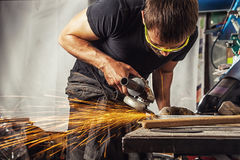 Man grinding metal with a angle grinder. A young man is a brunette welder wearing a black T-shirt and safety goggles grinding metal with a angle grinder in the Royalty Free Stock Images