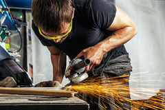 Man grinding metal with a angle grinder. A young man is a brunette welder wearing a black T-shirt and safety goggles grinding metal with a angle grinder in the Stock Photography
