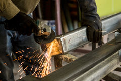 Man grinding piece of steel sparks flying. Worker wearing gloves grinding a piece of steel to smooth after welding Royalty Free Stock Images