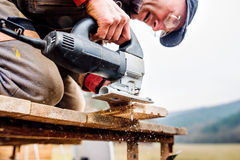 Man grinding planks of wood for home construction. Carpenter with grinder. Man grinding planks of wood for home construction Stock Photos