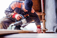Man grinding planks of wood for home construction. Royalty Free Stock Photo