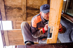Man grinding planks of wood for home construction. Stock Photos