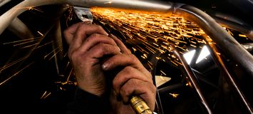 Man grinding steel tubing with a hot pneumatic grinding disc showering sparks royalty free stock photos