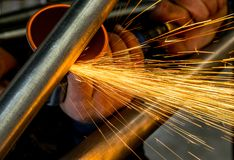 Man grinding steel tubing with pneumatic grinding disc showering sparks royalty free stock images