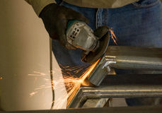 Man grinding steel. Man working with disc grinder after welding with sparks flying Royalty Free Stock Images