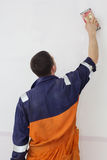 Man grinding white wall with sandpaper, back view. Handyman is doing grinding works with sandpaper on a white wall Royalty Free Stock Images