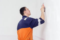 Man grinding white wall with sandpaper. Handyman is doing grinding works with sandpaper on a white wall in room Royalty Free Stock Photography