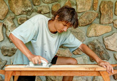 Man grinding wooden plank. Young man grinding wooden plank so he can use it for his new floor Royalty Free Stock Photo