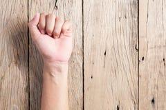 Man gripen hårt om näve på wood bakgrund royaltyfri fotografi