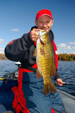 Man Fishing Holding Smallmouth Bass. A man grips a smallmouth bass he caught while freshwater fishing Stock Photography
