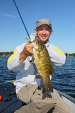 Man Fishing Holding Smallmouth Bass. A man grips a smallmouth bass he caught while freshwater fishing Stock Image