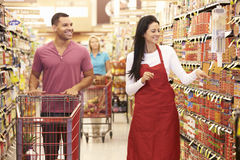 Man In Grocery Aisle Of Supermarket With Sales Assistant royalty free stock photography