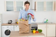 Man With Grocery Bag In Kitchen Room Stock Images