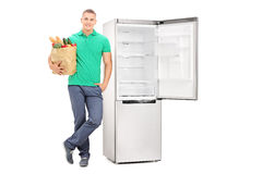 Man with grocery bag standing by an empty fridge Stock Photos