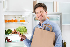 Man With Grocery Bag Standing Near The Open Fridge Stock Photo