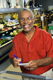 Man with grocery list. Middle aged African American man in grocery store holding shopping list and smiling at viewer stock photos