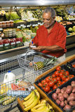 Man grocery shopping. Middle aged African American man in grocery store writing on shopping list stock image