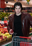 Man grocery shopping. In a grocery store royalty free stock photo
