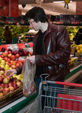 Man grocery shopping. In a grocery store Royalty Free Stock Images