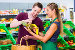 Man grocery shopping in corner shop. Man consulting organic supermarket clerk while grocery shopping Stock Image