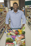 Man With Grocery Shopping In Supermarket Aisle Royalty Free Stock Photos