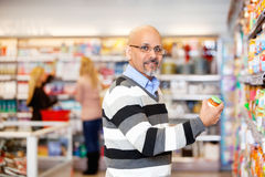 Man in Grocery Store. Portrait of a mature man shopping in the supermarket with people in the background royalty free stock image