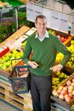 Man in Grocery Store. Mid adult man carrying shopping basket and looking at camera while shopping in fruit store stock image