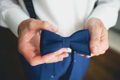 A man, a groom or a businessman in a stylish suit holding a blue bow tie, a fashion accessory. Preparing the groom for the wedding royalty free stock photo