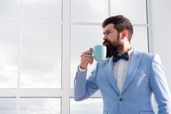 Man groom drinking coffee early in morning. Beginning of great day. Important day in his life. Get ready. Enjoy every. Minute. Hipster in tuxedo with bow tie royalty free stock photo