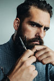 Man grooming his beard with scissors Royalty Free Stock Image