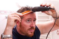 Man grooming his hair with electric razor Royalty Free Stock Images