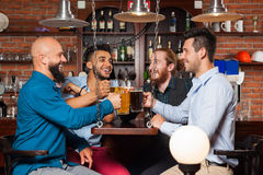 Man Group In Bar Clink Glasses Toasting, Drinking Beer Hold Mugs, Mix Race Cheerful Friends Wear Shirts Royalty Free Stock Photo