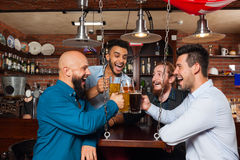 Man Group In Bar Clink Glasses Toasting, Drinking Beer Hold Mugs, Mix Race Cheerful Friends Wear Shirts Royalty Free Stock Images