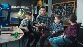 Man with kids exploring mechanical cartboard hand stock video