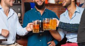 Man Group dans la barre font tinter des verres grillant Sit At Table, buvant haut étroit de tasses de prise de bière Photographie stock