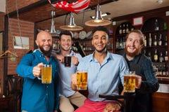 Man Group dans la barre font tinter des verres grillant, tasses potables de prise de bière, chemises gaies d'usage d'amis de cour Photo stock