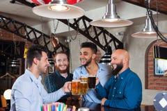 Man Group dans la barre font tinter des verres grillant, tasses potables de prise de bière, chemises gaies d'usage d'amis de cour Photos libres de droits