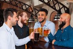Man Group dans la barre font tinter des verres grillant, tasses potables de prise de bière, chemises gaies d'usage d'amis de cour Photographie stock libre de droits