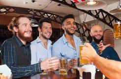 Man Group dans la barre tiennent des verres de bière, se tenant au barman de contre- ordre, les amis gais de course de mélange Images libres de droits