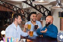 Man Group dans la barre tiennent des verres parlant, tasses de bière potables, chemises gaies d'usage d'amis de course de mélange Image libre de droits