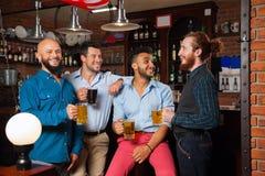 Man Group dans la barre tiennent des verres parlant, tasses de bière potables, chemises gaies d'usage d'amis de course de mélange Photographie stock