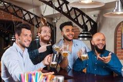 Man Group dans la barre tiennent les verres de bière vides, se tenant au barman de contre- ordre, les amis gais de course de méla Photos libres de droits